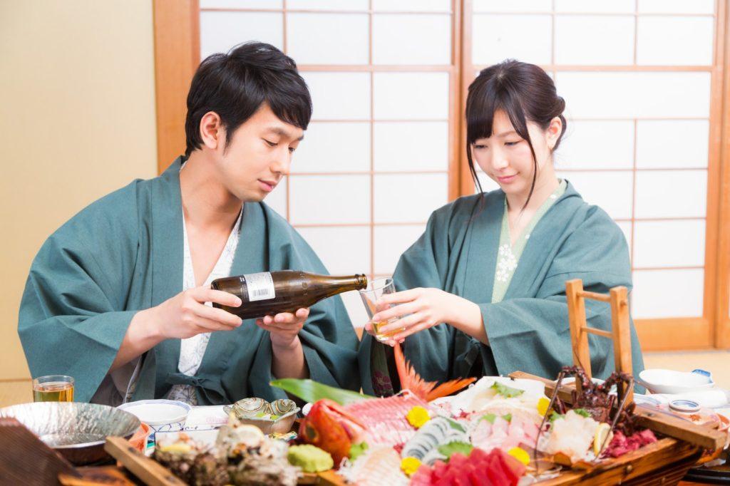 温泉の個室で料理を楽しむカップル